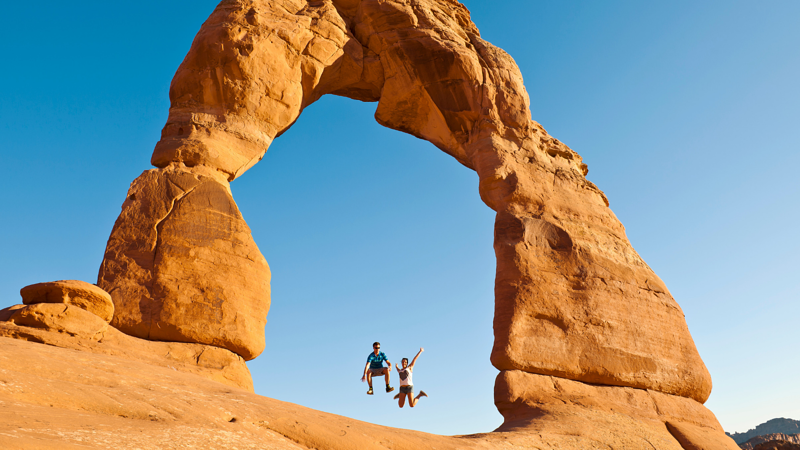 Couple jumping under rock arch